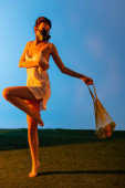 Photo barefoot woman in gas mask posing while holding reusable string bag with fruits on blue
