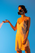 Photo woman in gas mask holding plastic bag on blue, ecology concept