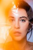 nahá žena dívá na kameru přes polyetylen na šedé, ekologie koncept