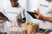 Selective focus of multiethnic volunteers with clipboards standing near packages with food and bottles of water