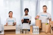 Multietničtí dobrovolníci se schránkou a jídlem při pohledu do kamery v blízkosti balíčků v charitativním centru