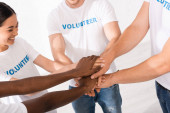 Selective focus of multiethnic volunteers in white t-shirts holding hands in charity center