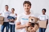 Selektivní zaměření muže držícího měkkou hračku v blízkosti multikulturních dobrovolníků s balíčky v charitativním centru