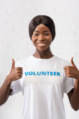 Photo African american volunteer showing thumbs up in charity center