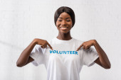 Photo African american volunteer pointing with fingers at t-shirt with lettering in charity center