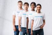 Selective focus of multicultural volunteers in t-shirts with lettering looking at camera
