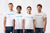 Young multiethnic people with volunteer lettering on t-shirts looking at camera