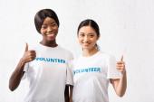Afričtí američtí a asijští dobrovolníci ukazující se jako gesto na kameru