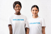 Asian and african american women with volunteer lettering on t-shirts looking at camera