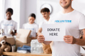 Selective focus of volunteer holding card with donate here lettering in charity center