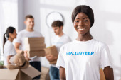Photo Selective focus of african american volunteer looking at camera in charity center