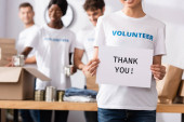 Photo Selective focus of volunteer holding card with thank you lettering near donations and multiethnic people