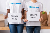 Cropped view of multiethnic volunteers holding card with donate here and today lettering in charity center