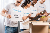 Photo Selective focus of volunteer holding card with donate here lettering near donations and multicultural people