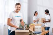 Selektivní zaměření dobrovolníka, který dává plechovky do krabice v charitativním centru