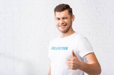 Volunteer winking and showing thumb up at camera stock vector