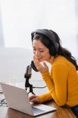 vzrušený asijský broadcaster v bezdrátových sluchátek pokrývající ústa s rukou při smíchu v blízkosti mikrofonu