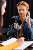 selective focus of redhead man gesturing during interview with young asian radio host writing in notebook