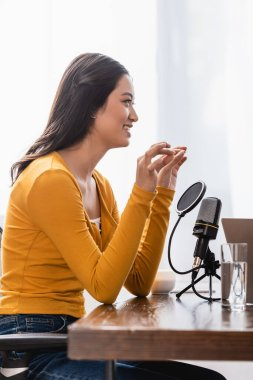 selective focus of asian broadcaster showing small amount gesture while sitting near microphone in studio