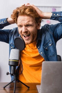 Angry announcer touching head while screaming in microphone at workplace stock vector