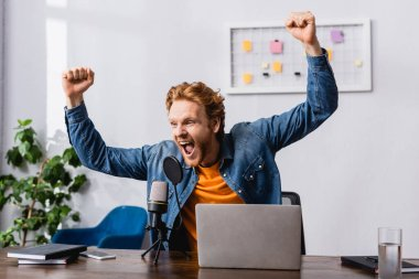 Excited announcer in denim shirt showing triumph gesture near microphone and laptop stock vector