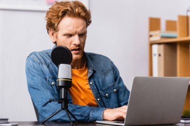Concentrated redhead radio host using laptop while sitting near microphone stock vector