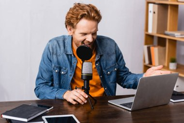Excited, redhead radio host gesturing while talking in microphone near laptop and notebooks stock vector
