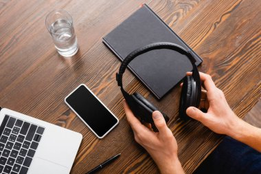 Cropped view of freelancer holding wireless headphones near smartphone with blank screen, laptop, notebook and glass of water stock vector
