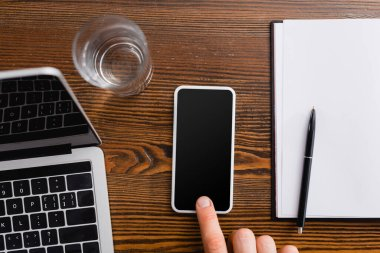 Cropped view of freelancer touching smartphone with blank screen near laptop, notebook and glass of water stock vector