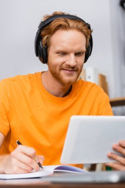 selective focus of redhead student in wireless headphones using digital tablet and writing in notebook