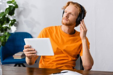 selective focus of pensive student touching wireless headphones while holding digital tablet and looking away