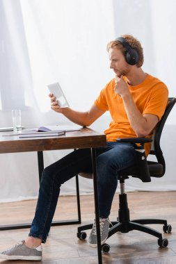 thoughtful student in wireless headphones using digital tablet while sitting at desk at home