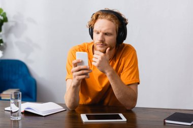 thoughtful student in wireless headphones touching chin while using smartphone at home