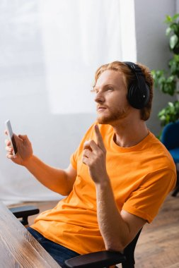 thoughtful man in wireless headphones showing idea gesture while holding smartphone