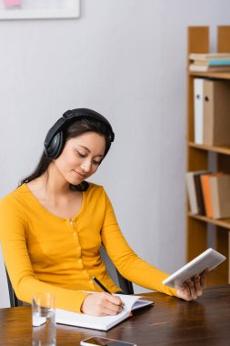 brunette asian student using digital tablet and writing in notebook while listening podcast in wireless headphones