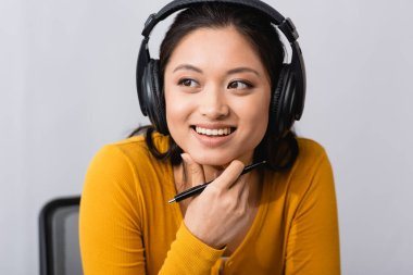 brunette asian woman in wireless headphones holding pen and touching chin while looking away
