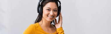horizontal image of brunette asian woman touching wireless headphones while looking at camera