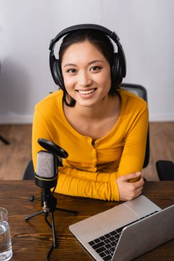 Excited asian announcer in wireless headphones looking at camera near microphone and laptop stock vector