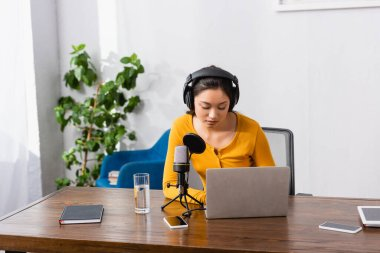 brunette asian broadcaster using laptop near microphone, glass of water and gadgets at workplace