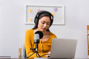 Concentrated asian radio host in wireless headphones using laptop near microphone in studio stock vector