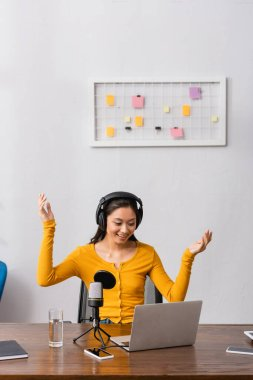 Excited asian broadcaster in wireless headphones showing wow gesture while working near microphone and laptop stock vector