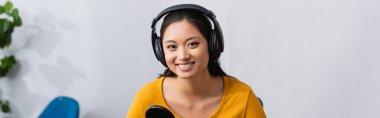 horizontal image of joyful asian broadcaster in wireless headphones looking at camera in radio studio