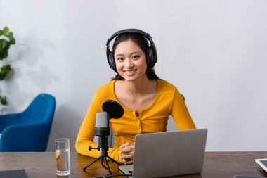joyful asian announcer in wireless headphones looking at camera while sitting near laptop and microphone