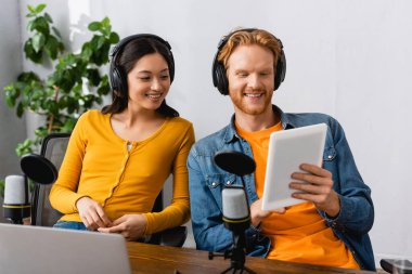 excited interracial broadcaster in wireless headphones looking at digital tablet at workplace