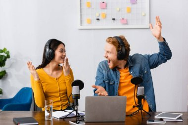excited multicultural broadcasters in wireless headphones gesturing and looking at each other at workplace