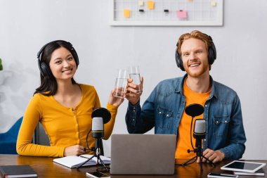 interracial couple of broadcasters in wireless headphones clinking glasses of water while looking at camera