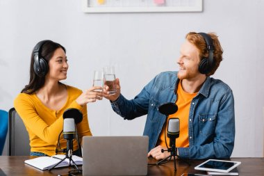 interracial couple of young radio hosts clinking glasses of water at workplace
