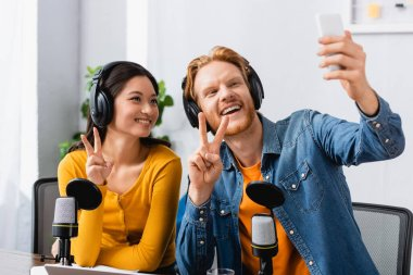 Excited, redhead announcer taking selfie on mobile phone while showing victory signs together with asian colleague stock vector