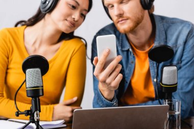 selective focus of young broadcaster using smartphone near asian colleague in wireless headphones