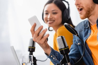 excited announcer using smartphone near asian coworker in wireless headphones